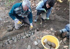 immagine di posa pietre per creazione canalina scolo su sentiero